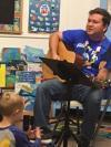 Joel playing guitar with child listening and watching.